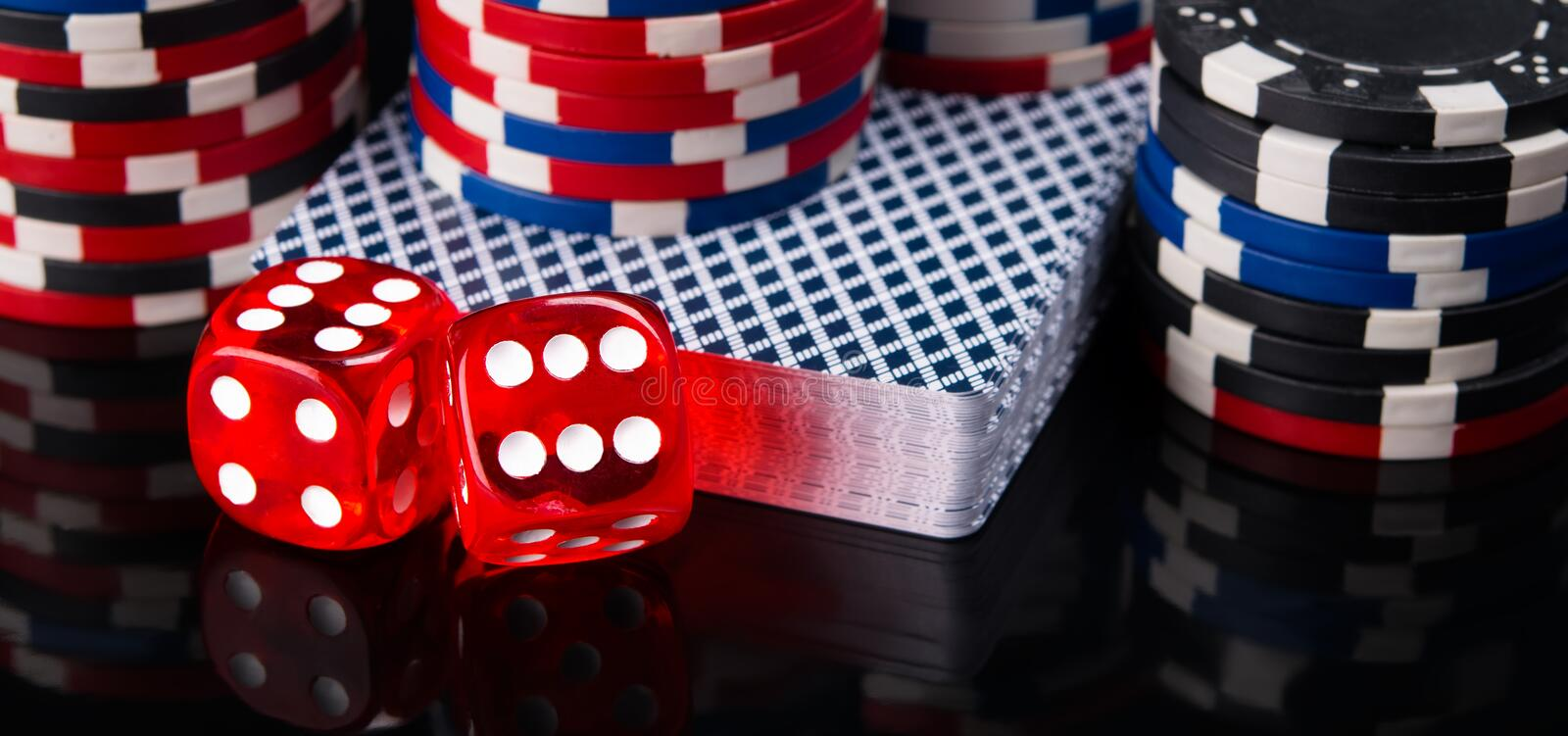 Two red dice, a deck of cards and poker chips, on a black background royalty free stock photo