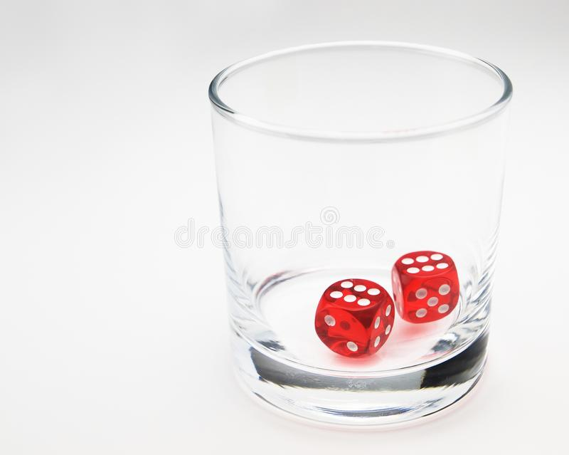Two red dice in a glass