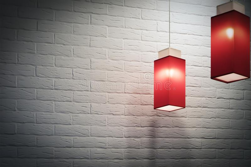 Two red elongated square pendant electric lamps against white brick wall royalty free stock photos