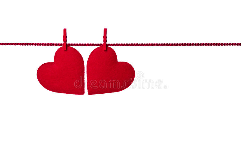 Two red felt hearts hanging on the rope on white background royalty free stock photo