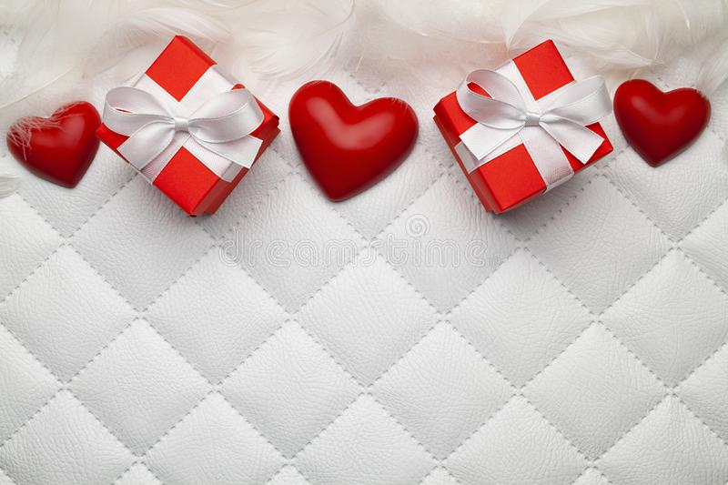 Two red gift boxes with white ribbons, feathers and three red heart on white leather background royalty free stock photo