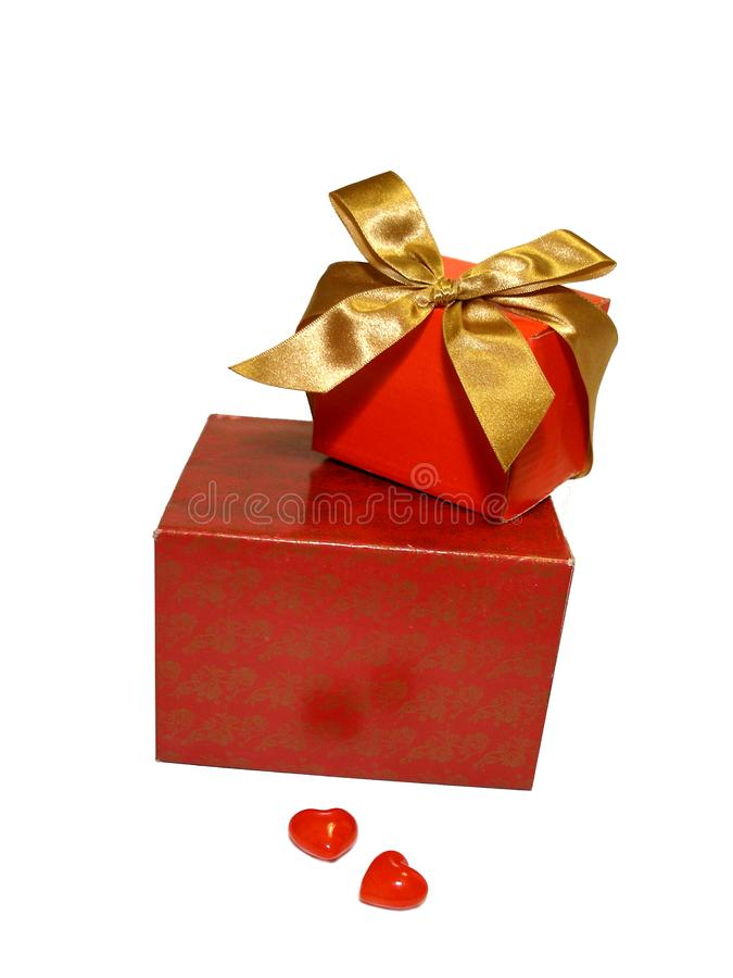 Two red gifts with a gold ribbon and two hearts