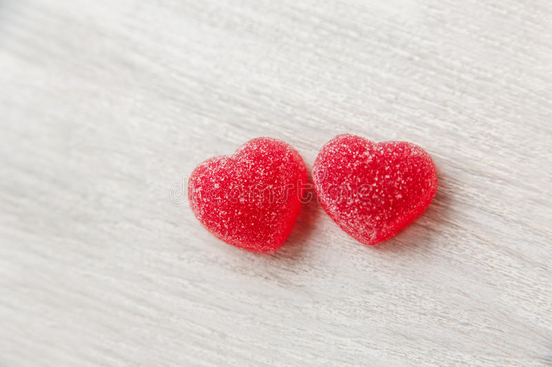 Two red heart shape jelly candy.white wooden table.space for tex royalty free stock photography