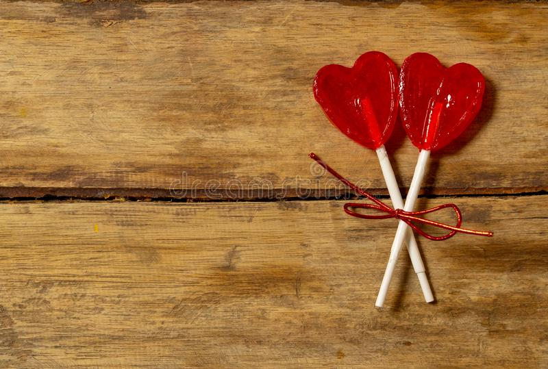 Conceptual Valentines image of Two cute red heart shaped lollipops on rustic wooden stock images