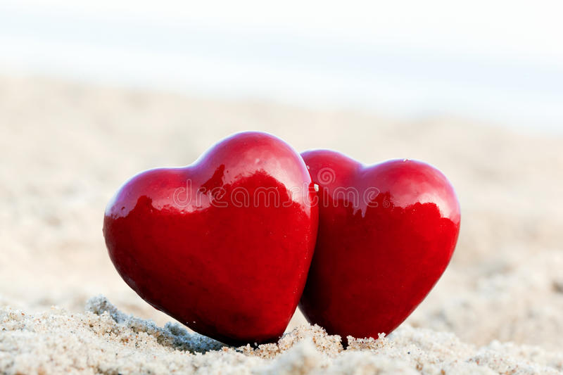Two red hearts on the beach. Love stock images
