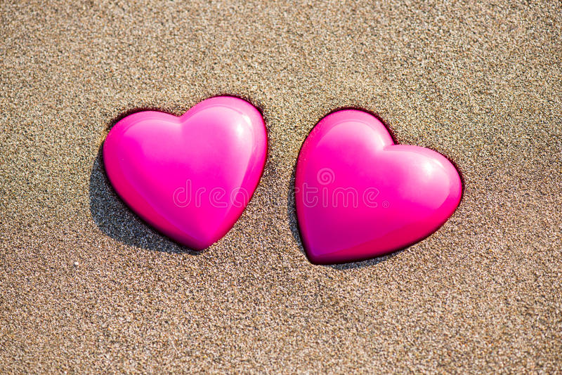 Two red hearts on the beach symbolizing love. Valentine's Day, romantic couple. Calm ocean in the background. Vintage, retro style royalty free stock photo