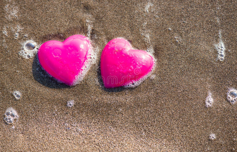Two red hearts on the beach symbolizing love. Valentine's Day, romantic couple. Calm ocean in the background. Vintage, retro style royalty free stock images
