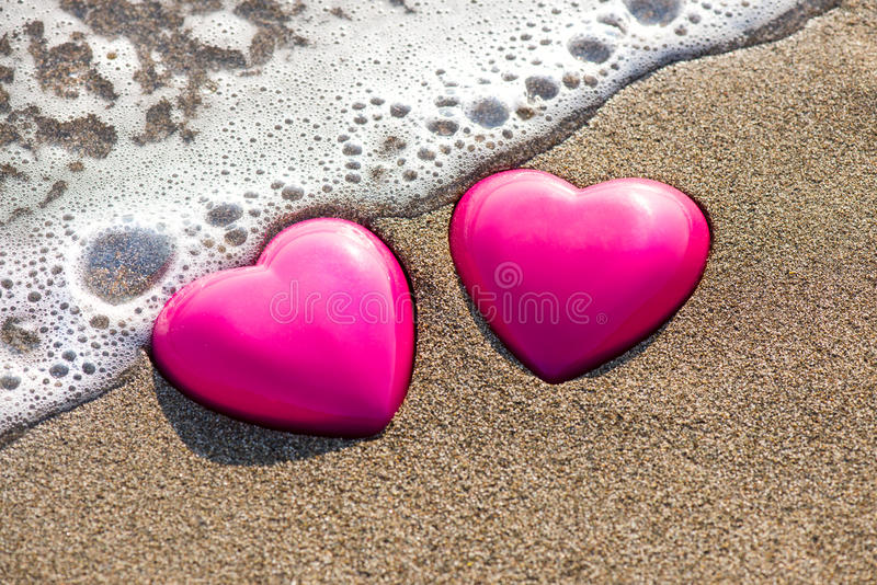 Two red hearts on the beach symbolizing love. Valentine's Day, romantic couple. Calm ocean in the background. Vintage, retro style stock photo