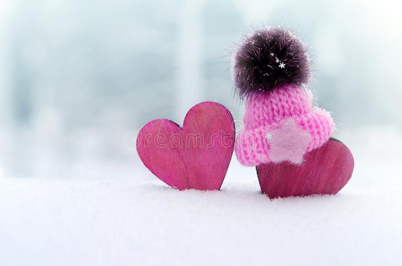 Two red hearts in cap on snow background. couple in love. Valentine`s Day. Red heart on snowy tree branch in winter. Holidays royalty free stock photo