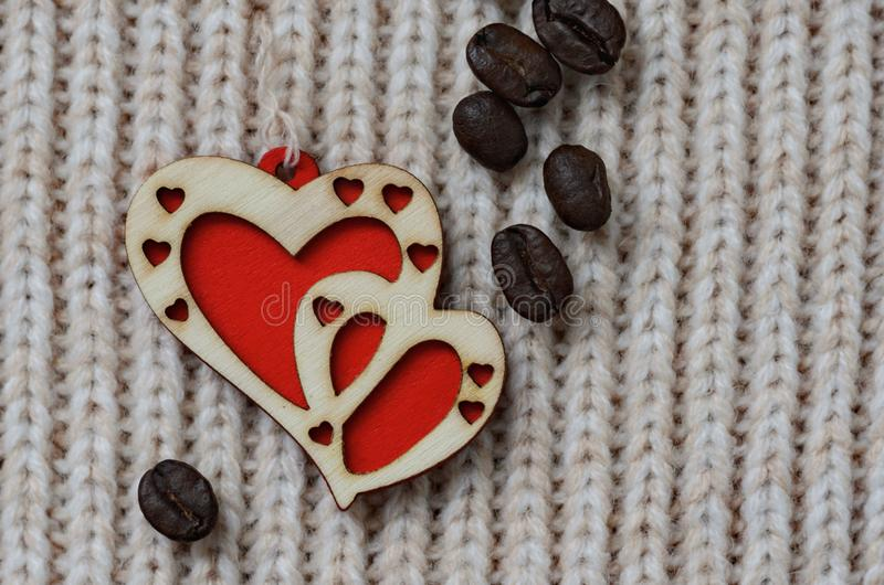 Two red hearts made of wood on a woolen knit background stock image