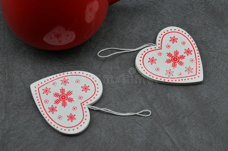 Two red hearts near red cup of tea stock images