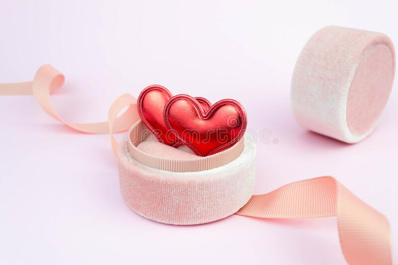 Two red hearts in a ring box with ribbon on soft pink background. Romantic symbol gift. Couple date concept royalty free stock photos