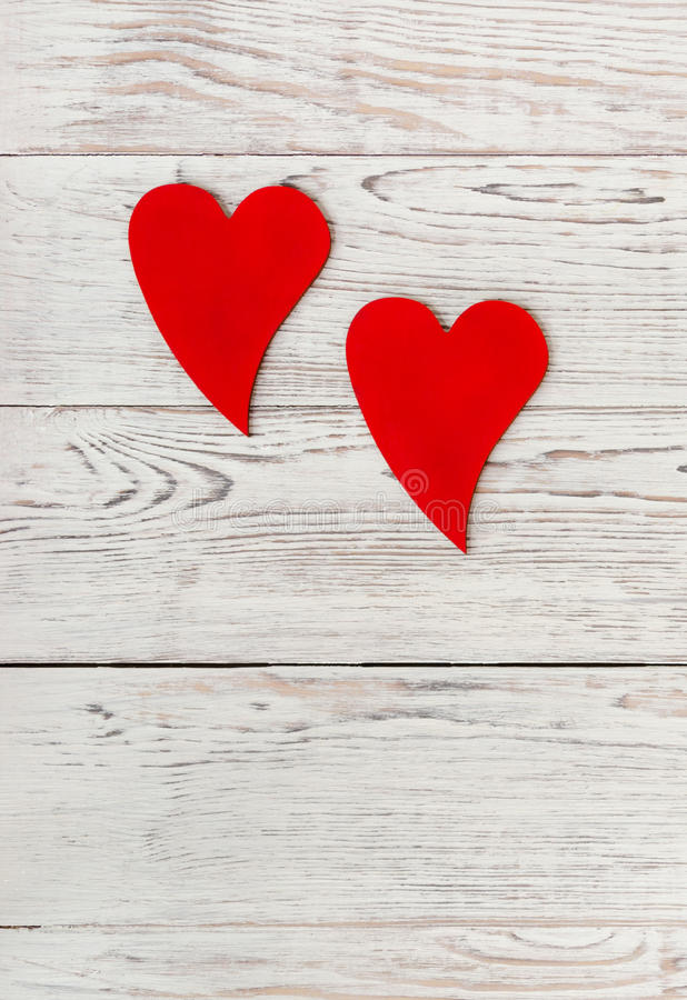 Two red hearts. On white wooden background. Love. Valentine`s Day concept. Copy-space composition royalty free stock photography