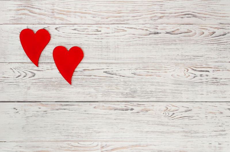 Two red hearts. On white wooden background. Love. Valentine`s Day concept. Copy-space composition stock photo