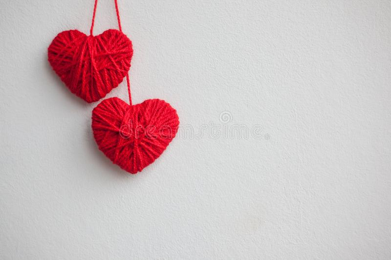 Two red hearts from woolen threads on a light background. Valentine`s day concept.  stock images