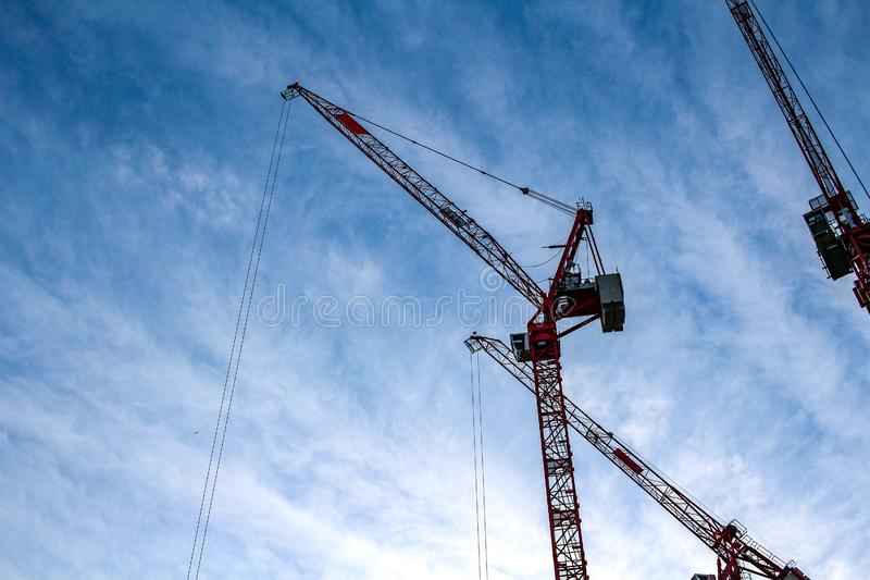 Two red industrial construction tower cranes against blue sky in the background - concept business real estate work erection. Technology building site progress stock photography