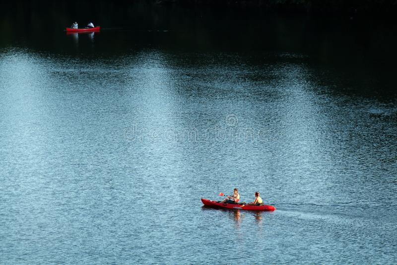 Two red kayaks navigating light and dark waters of Colorado river as seen from Congress bridge in Austin. AUSTIN, TEXAS - SEPTEMBER 30, 2017: Two red kayaks stock photos