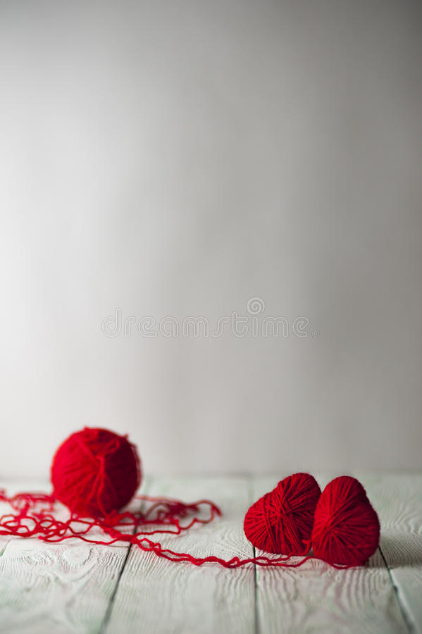 Two red knitted hearts and a ball of yarn stock photography