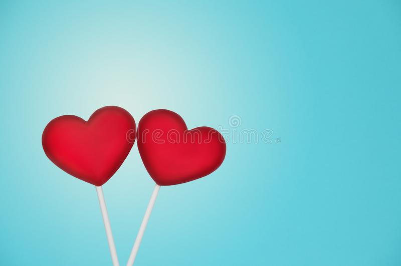 Two Red Lollipops Shape of the Heart on Light Blue Background. Valentine`s Day Concept. stock photography