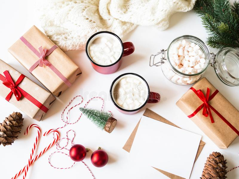 Two red mugs with hot drink and marshmallows, paper card for letter, envelope and xmas decoration. Flat lay for Merry Christmas or stock photo