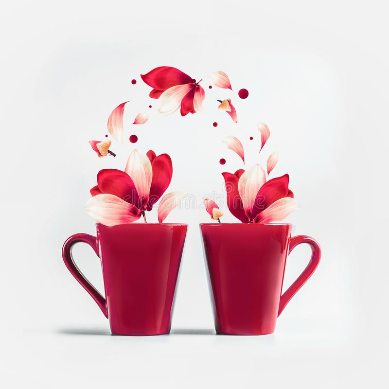 Two red mugs with red white flying flowers and petals of Amaryllis flowers standing on white background. Creative couples concept royalty free stock images