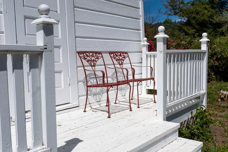 Two red ornate metal chairs on a white wooden porch royalty free stock image
