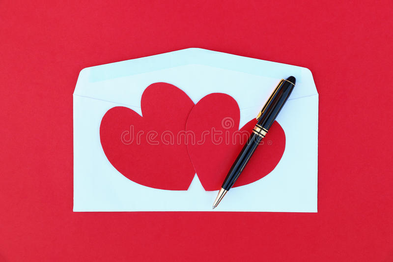 two red paper hearts on white envelope and black business pen royalty free stock images