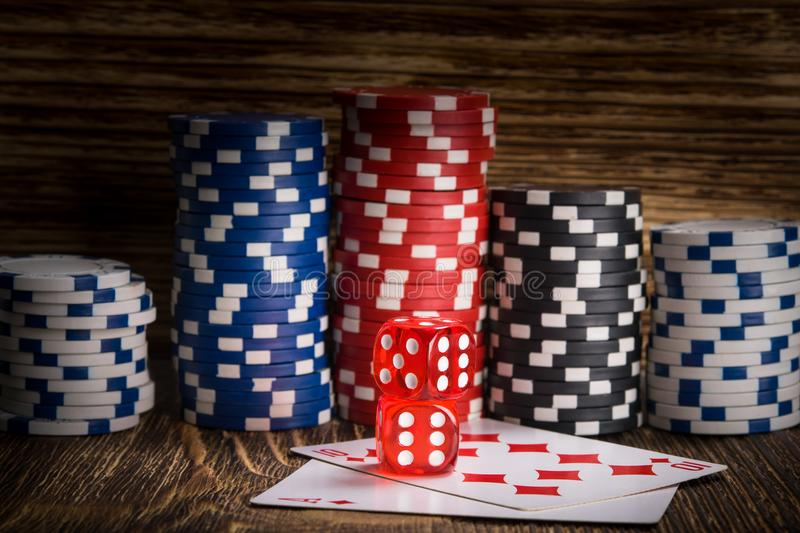 Two red poker cube lie on the cards against the background of poker chips royalty free stock image