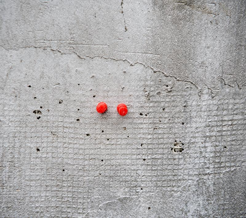 Two Red Push Pins on a wall. Two Red Push Pins on a concrete wall royalty free stock image