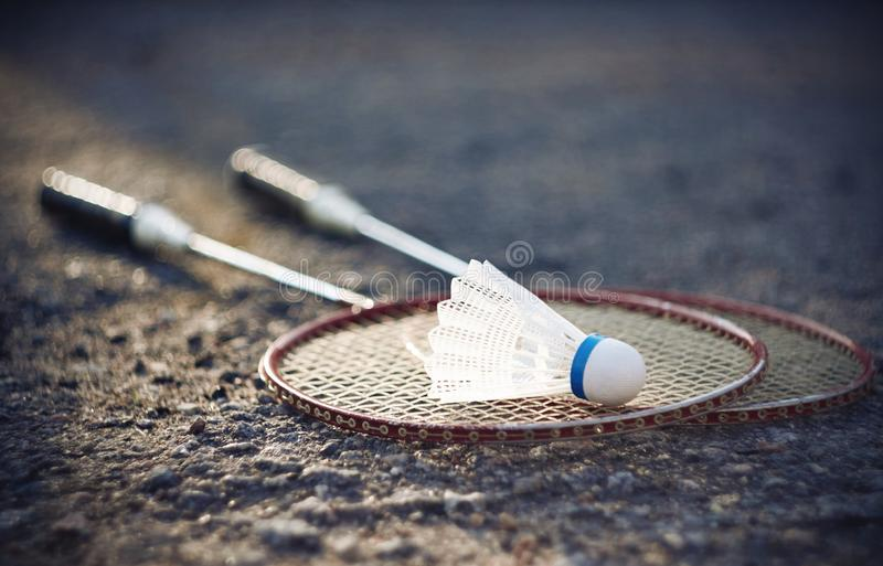 Two red racquets for badminton and a white shuttlecock. Two old red racquets for badminton and a white new shuttlecock with a blue strip lie on the asphalt stock photos