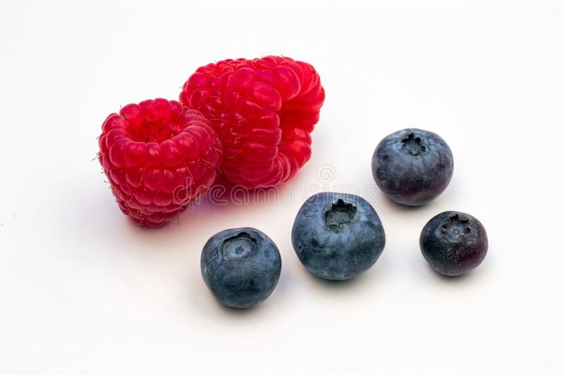Two Red Raspberries and Four Blueberries. Closeup of Two Red Raspberries and Four Plump Blueberries on a white background royalty free stock photo