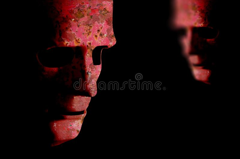 Two red rusting old decaying robot faces. Two robot faces with red rusting decaying skin showing old technology. Black background space for text royalty free stock image