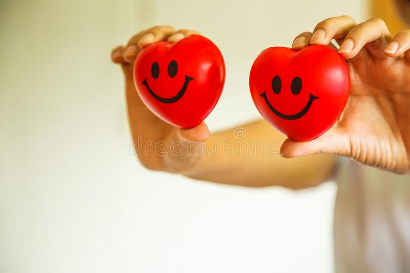 Two Red Smiling Hearts held by female nurse`s hands, representing giving effort high quality service mind to patient. Profession. Al, Specialist in white uniform stock image