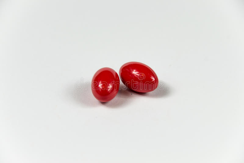 Two red soft gelatine capsules. Two red soft gelatine capsules in bright light stock photo