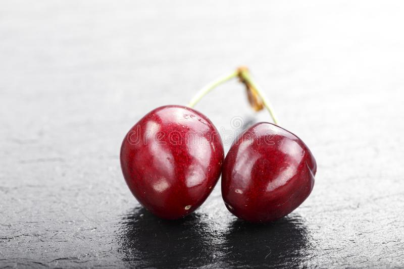 Two red sweet cherries on a handle against a black background. stock images