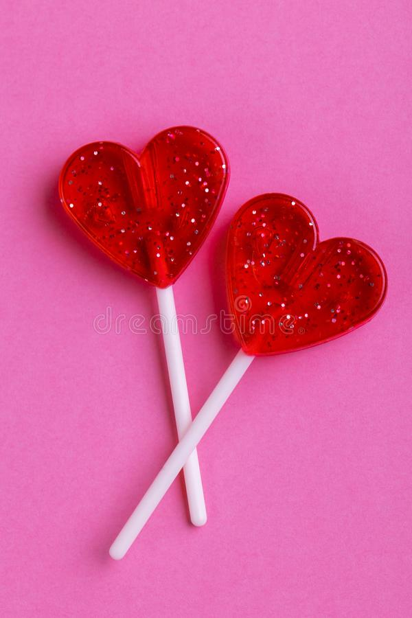 Two red sweet tasty lollipops in shape of heart stock images