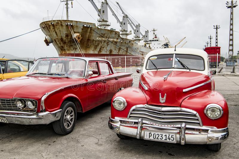 Red american classic cars and rusty ship, Santiago de Cuba stock image