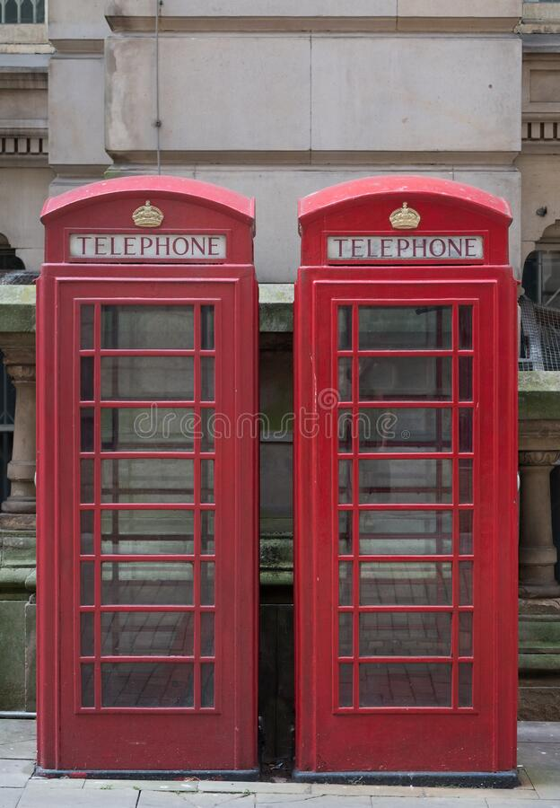 Two red telephone boxes on street royalty free stock images