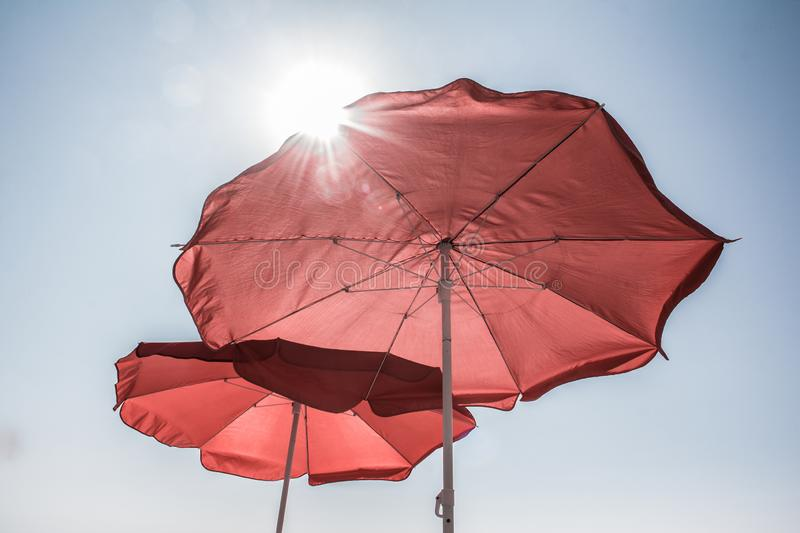 Two red umbrellas from the sun. Summer. Heat. Sunlight. Sun protection.  clear sky. sunny day stock images