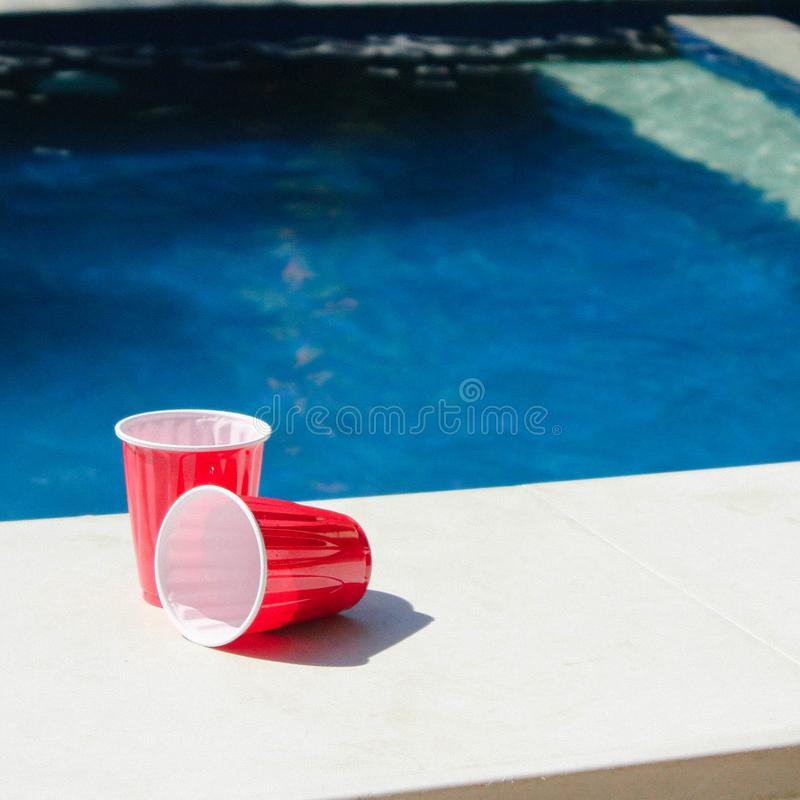 Two Red-and-white Disposable Cups on Gray Ceramic Tiles Photo royalty free stock photography