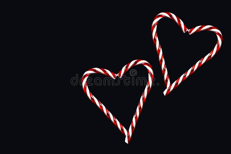Two red and white striped traditional Christmas candy canes forming two hearts on black background stock images