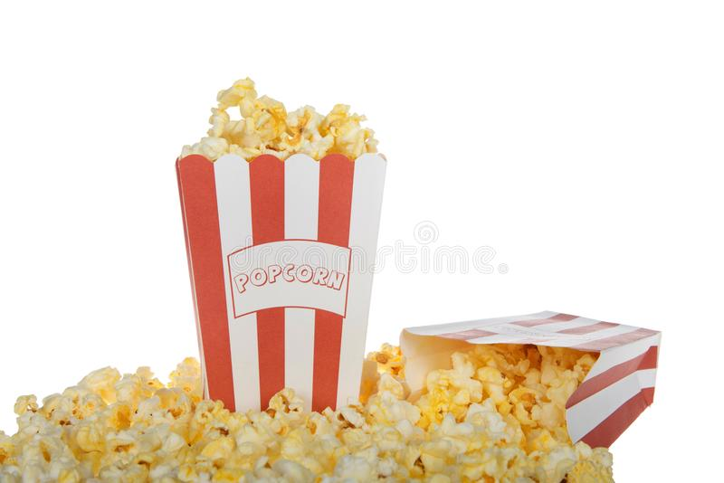 Two bags of butter popcorn isolated on white background. Two red and white stripped bags labeled POPCORN filled with fresh butter popcorn one bag knocked over royalty free stock photos