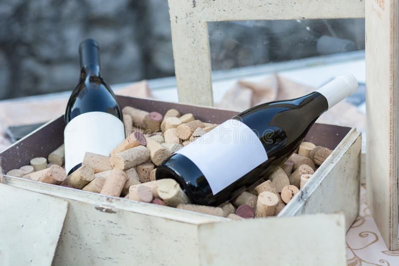 Two red wine bottles in old wooden box full with corks stock photo