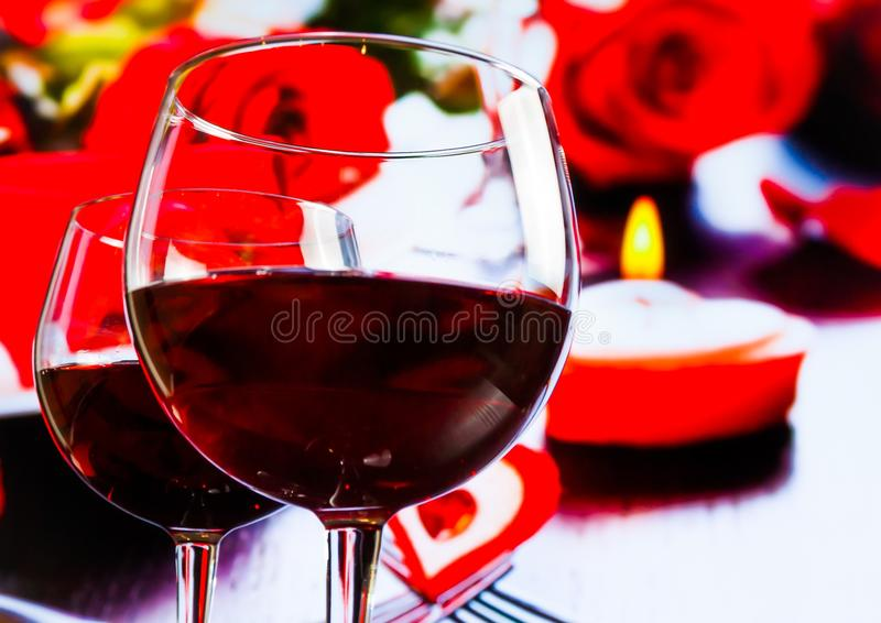 Two red wine glasses on blur hearts and roses decoration background. Festive and love concept stock photo