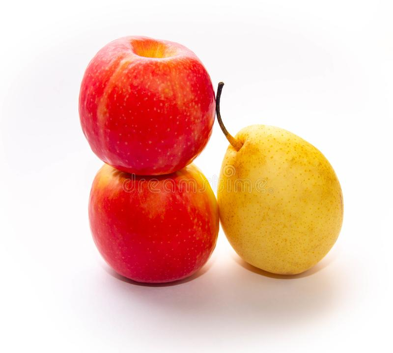 Two red-yellow apples and one pear on a white background stock image