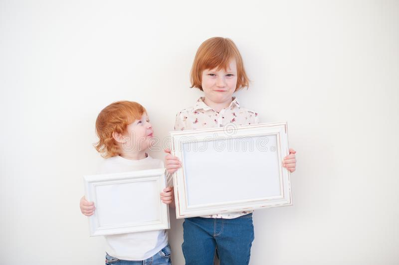 Two redhead children with frames. In their hands royalty free stock photos