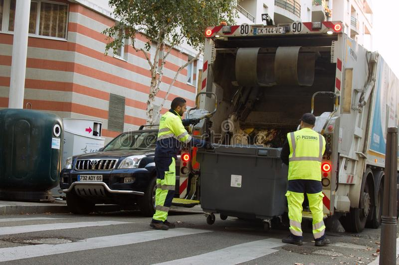 Two refuse collection workers loading garbage into waste truck emptying containers royalty free stock images