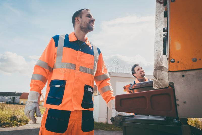 Two refuse collection workers loading garbage into waste truck. Emptying containers royalty free stock image
