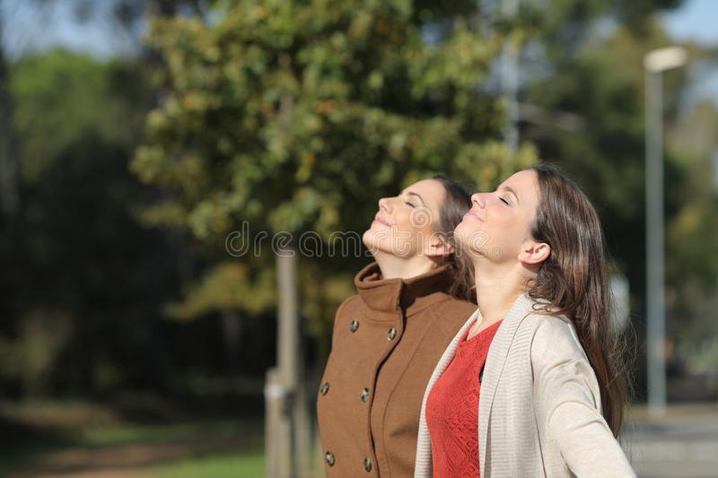Two relaxed women breathing fresh air in winter in a park royalty free stock images