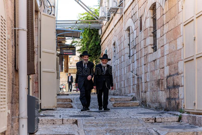 Two religious Jews walk and talk down the street near Jaffa Gate in the old city of Jerusalem, Israel. Jerusalem, Israel, November 17, 2018 : Two religious Jews stock images